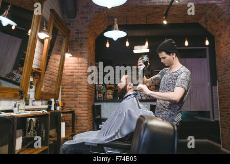 Young attractive hairdresser with tatoo in black hat drying man's hair with blowdryer in hair salon - Stock Photo