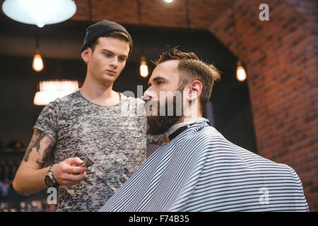 Concentrated skillful hairdresser making haircut to young bearded handsome man at barbershop - Stock Photo