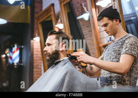 Barber making haircut to handsome attractive man with beard and working with electric razor - Stock Photo