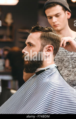 Professional hairdresser cutting young bearded man's hair in hairdressing salon - Stock Photo
