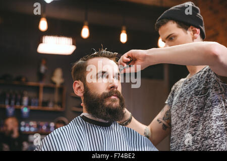Handsome skillful barber cutting hair of young attractive man with beard at barbershop - Stock Photo
