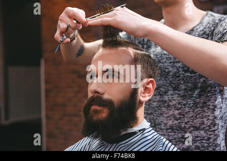 Portrait of young handsome man with beard having a haircut with comb and scissors in hair salon - Stock Photo