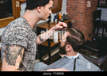 Young hairstylist with tatoo combing hair of male client with a comb in hair salon - Stock Photo