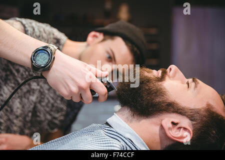 Attractive bearded man getting his beard shaved by modern barber in barber shop - Stock Photo