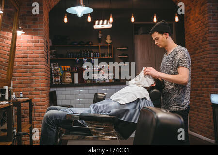 Barber finishing grooming and taking care of client's face in barbershop - Stock Photo