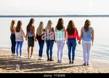 Eight teenage girls standing side by side holding hands while looking out to sea at Broughty Ferry beach in Dundee, - Stock Photo