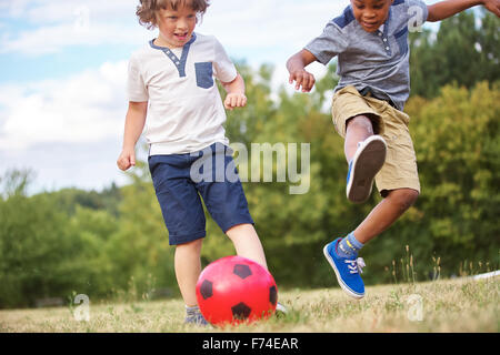 Children playing soccer and having fun in summer - Stock Photo