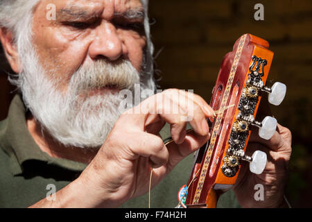Guitar maker Sistos Pasaye strings one of his products outside a shop in Paracho, Michoacan, Mexico. - Stock Photo