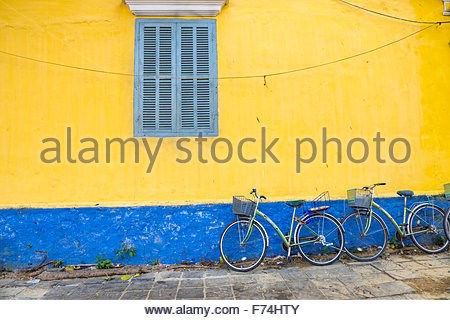 Bicycles against a colorful wall, Hoi An Ancient town, Quang Nam Province, Vietnam - Stock Photo