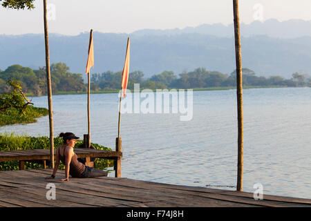 A young woman sits on the docks of Catemaco Lake in Veracruz, Mexico. - Stock Photo
