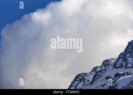 Cumulonimbus cloud developping behind mountain in the Alps - Stock Photo