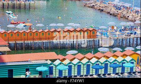 Striped beach huts on piers in the Tyrrhenian Sea Amalfi Coast Salerno Campania Italy Europe - Stock Photo