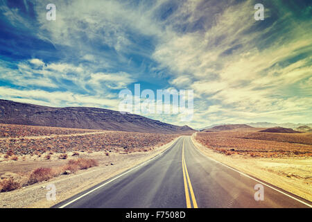Vintage stylized endless country highway in Death Valley, California, USA. - Stock Photo