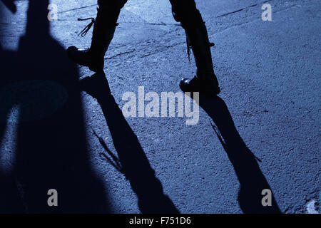 Blue shadows and silhouette of an unrecognizable woman in combat boots walking down a New York City street - Stock Photo