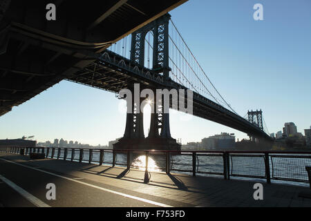 The sun rises over Brooklyn and casts deep shadows on the East River Esplanade, New York, under the Roosevelt overpass - Stock Photo