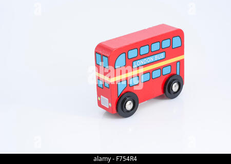 Red London bus wooden toy on white background - for London Transport & Transport for London (TFL). Metaphor for - Stock Photo