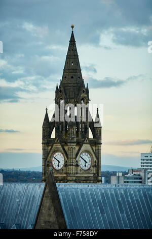 Manchester skyline showing the rooftops and the clock tower of the town hall    tower light shaft rays through clouds - Stock Photo