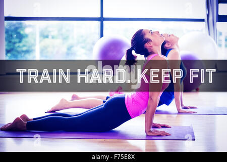 Composite image of fit women doing the cobra pose in fitness studio - Stock Photo