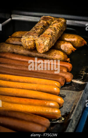Rows and stacks of grilling hot dogs, Italian Sausages and Bratwurst on black iron cooktop outdoors - Stock Photo