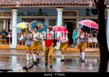 Schoolchildren, students cross a road in Vinales, rain, umbrellas, eating ice cream, Viñales, Cuba, Pinar del Rio, - Stock Photo