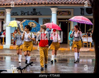 Schoolchildren, students cross a road in Vinales, rain, umbrellas, eating ice cream, Viñales, Cuba, Pinar del Rio, - Stock Photo