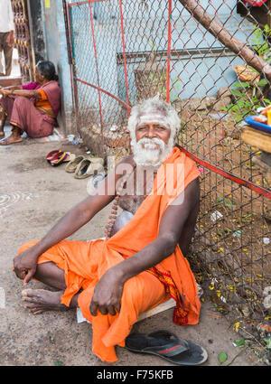 Old man devotee dressed wearing saffron robe sitting outside the Kapaleeswarar Temple, a Hindu temple of Shiva, - Stock Photo