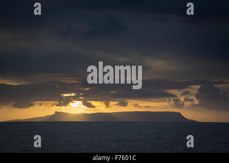 Dark clouds and sunset over the Isle of Eigg, Sound of Sleat, Highlands, Scotland - Stock Photo