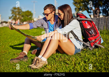 Young couple siting on the grass and examining the map - Stock Photo