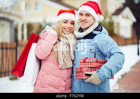 Young couple in Santa Claus hats holding gifts - Stock Photo
