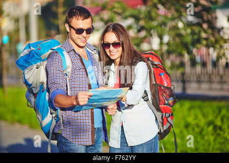 Couple of travelers looking at map together in the city - Stock Photo