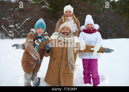 Cheerful family of four having fun in winter park - Stock Photo
