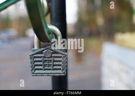 Padlock in form of house hanging on green metal arc - Stock Photo