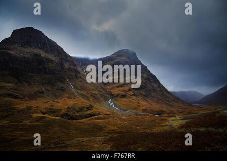 Heavy dark storm clouds gather over the Pass of Glen Coe, Lochaber, Highlands, Scotland - Stock Photo