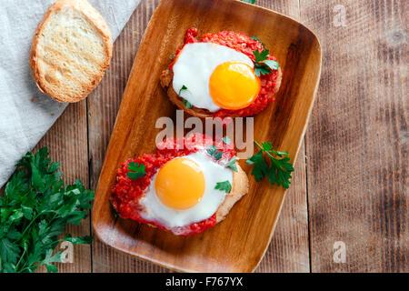 fried eggs with tomato sauce on bruschetta - Stock Photo
