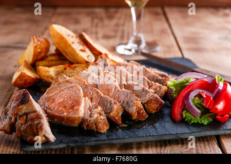 Sliced pork steak with fried potatoes - Stock Photo