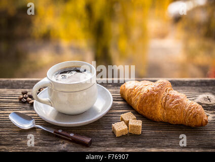 Croissant and coffee, blurred autumnal sunshine on background - Stock Photo