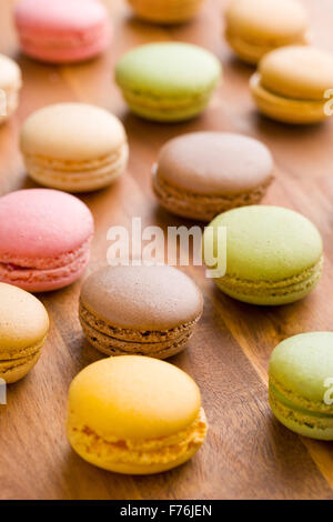 tasty colorful macarons on wooden table - Stock Photo