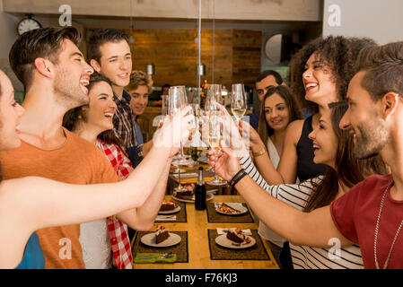 Group of friends toasting and looking happy at a restaurant - Stock Photo