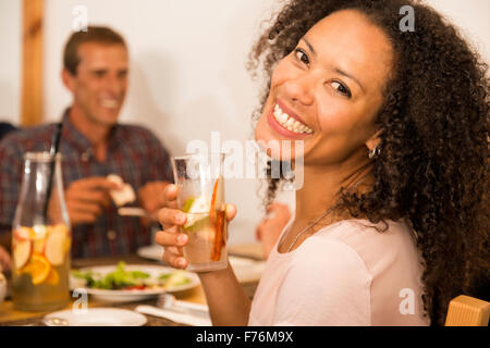 Happy Afro-American woman at the restaurant having a drink - Stock Photo