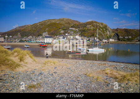 A view over the shingle beach towards Barmouth town and harbour with small houses scattered on th the surrounding - Stock Photo