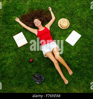 Beautiful and happy young woman lying on the grass - Stock Photo