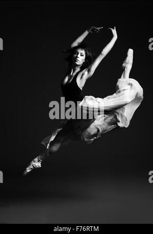 Ballet dancer in striking flying pose, black and white image - Stock Photo