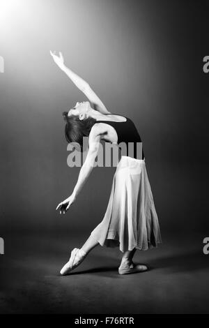 Ballet dancer looking into the light in graceful pose - Stock Photo
