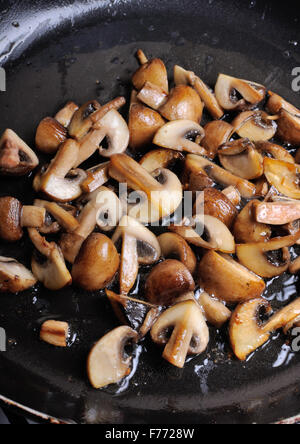 Fried sliced mushrooms in butter in a frying pan. For step by step recipe - Stock Photo