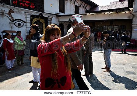 a beautiful blonde girl taking selfie at Pashupatinath temple in Kathmandu - Stock Photo