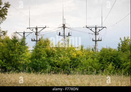 Electric power transmission pillars or power grid pylon wires, four electrical high energy towers construction in - Stock Photo