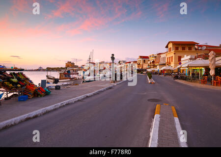 View of the seafront with coffee shops, bars and restaurants and fishing boats in the harbour of Aegina island, - Stock Photo