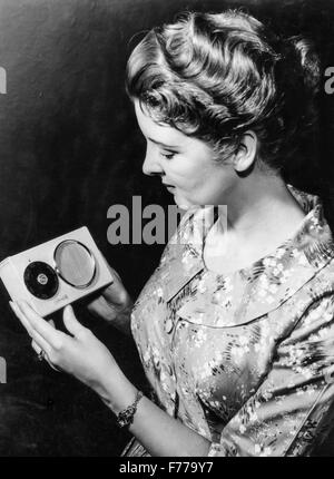 a woman with a powered by solar energy portable radio,1957 - Stock Photo