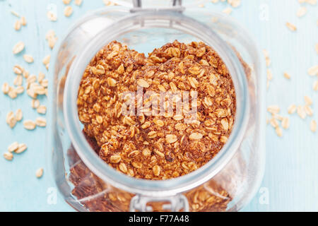 Homemade oatmeal banana cookies in the jar surrounded by oatmeal on blu wooden table - Stock Photo