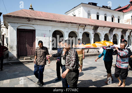 people carrying a corpse of a man to the cremation place for funeral in Pashupatinath temple complex in Kathmandu, - Stock Photo